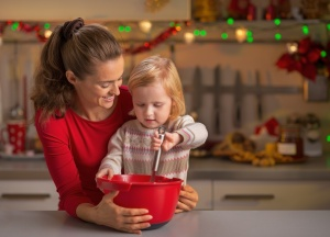 Happy mother and baby whisking dough in christmas decorated kitchen